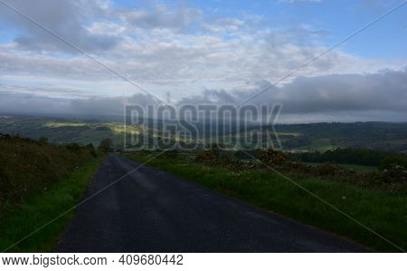 Dark Storm Clouds Hovering Over A Wide Dirt Road.