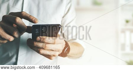 Business Man Using Smart Phone In Office. Communication And Technology Concept. Banner Copy Space