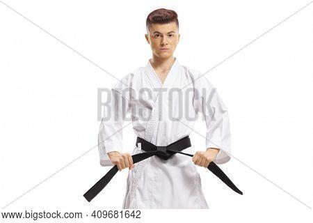 Guy in karate kimono holding his black belt isolated on white background