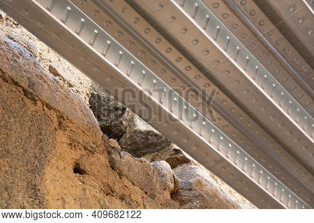 Detail Of Metal Decking Sheet And Old Stone Wall On Construction Site. Composite Decking For Restora