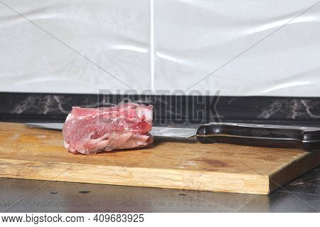 Cut Pieces Of Raw Meat With A Large Knife On A Cutting Board Close-up