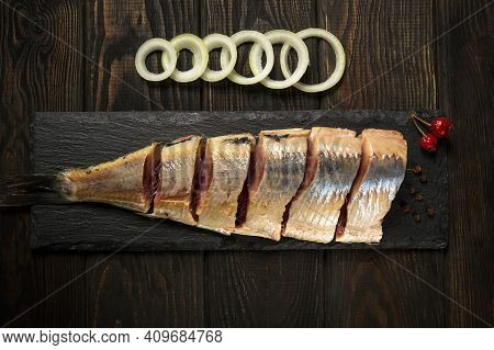 Raw Norwegian Herring With Onions And Spices On A Serving Board Close Up. The Idea Of Snack For A St