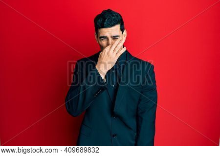Handsome hispanic man wearing business clothes smelling something stinky and disgusting, intolerable smell, holding breath with fingers on nose. bad smell