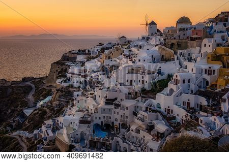 Oia Village Santorini With Blue Domes And White Washed House During Sunset At The Island Of Santorin