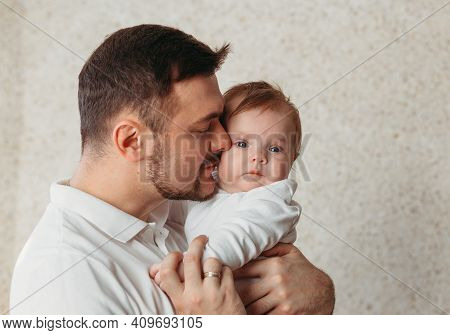 A Gentle Portrait Of A Young Father And Baby Daughter On A Bright Background. Tenderness, Parenthood
