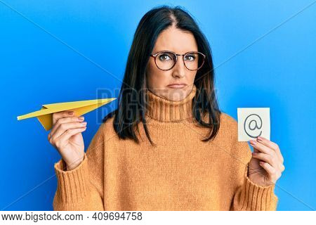 Middle age brunette woman holding email symbol and paper plane depressed and worry for distress, crying angry and afraid. sad expression.