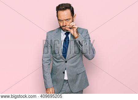 Middle age man wearing business clothes mouth and lips shut as zip with fingers. secret and silent, taboo talking