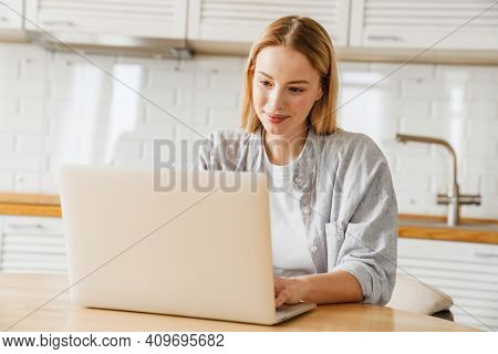 Pleased blonde girl smiling and using laptop while sitting at home kitchen