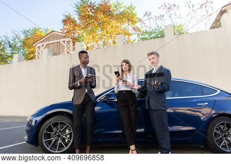 Young Confidence Business Partners, African Man And Caucasian Man And Woman, Are Working Using Table