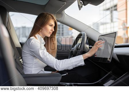 Smart Electric Car Concept. Pretty Woman In Formal Wear, Controlling Modern Electric Self-steering C
