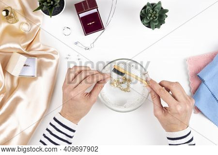 Woman Hands Cleaning And Polishing Jewelry Necklace With Homemade Jewelry Cleaner At Home. Top View