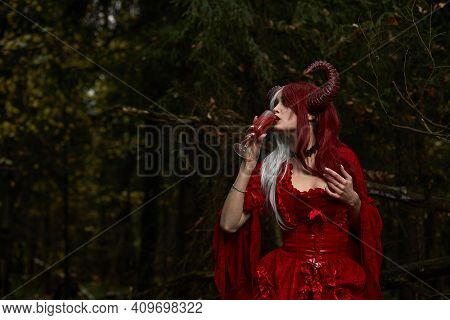 Stylish And Fashionable Model Girl In The Image Of Maleficent Posing Among Mystic Forest - Fairytale