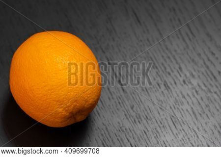 Orange On Black Wooden Background Close Up With Copy Space