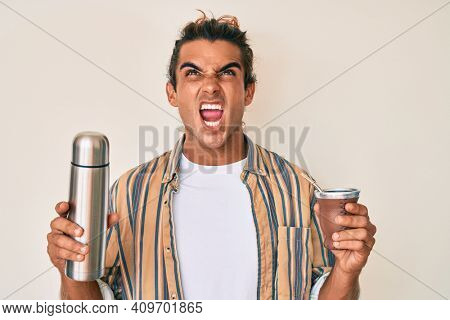 Young hispanic man drinking mate infusion angry and mad screaming frustrated and furious, shouting with anger looking up.