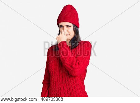 Young beautiful girl wearing sweater and wool cap smelling something stinky and disgusting, intolerable smell, holding breath with fingers on nose. bad smell
