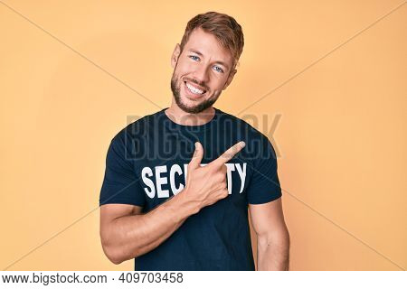 Young caucasian man wearing security t shirt cheerful with a smile of face pointing with hand and finger up to the side with happy and natural expression on face