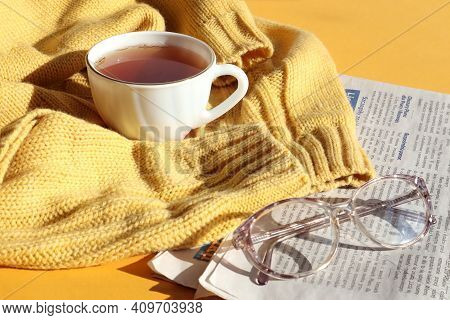 Glasses For Vision With A Cup Of Hot Tea On A Knitted Sweater, A Fresh Newspaper, A Side View-the Co