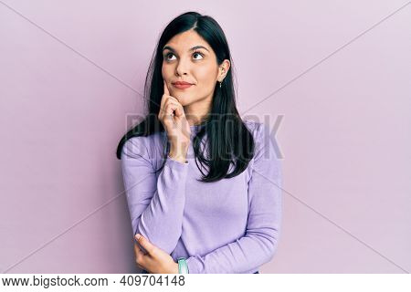 Young hispanic woman wearing casual clothes with hand on chin thinking about question, pensive expression. smiling and thoughtful face. doubt concept.
