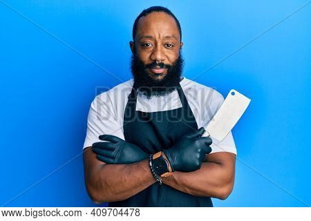 Young african american man wearing professional apron holding knife relaxed with serious expression on face. simple and natural looking at the camera.