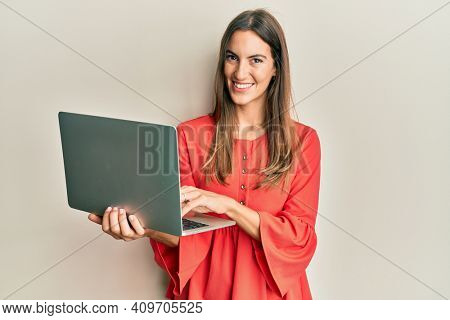 Young beautiful woman working using computer laptop looking positive and happy standing and smiling with a confident smile showing teeth