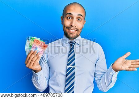 Hispanic adult business man holding swiss franc banknotes celebrating achievement with happy smile and winner expression with raised hand