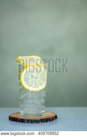 Glass Of Water With Ice And Sliced Lemon Put On Wooden Saucer. Homemade Summer Drink