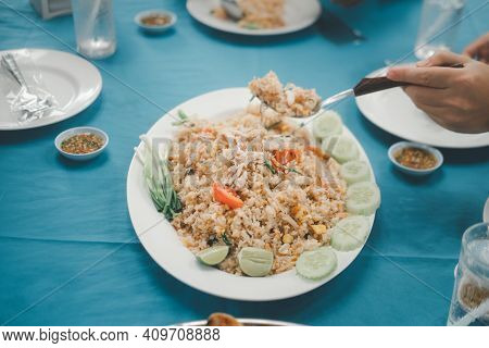 Man Scoop Seafood Fried Rice Put On The Central In The Table