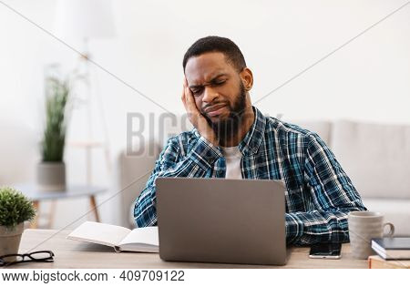 Boring Job. Unhappy African Man At Laptop Working Online Sitting In Modern Office. Business Issues,