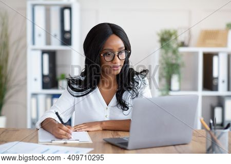 Happy Black Young Business Lady Working On Laptop At Office. Focused African American Woman Taking N