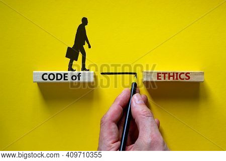 Code Of Ethics Symbol. Wooden Blocks With Words 'code Of Ethics'. Businessman Hand. Businessman Icon