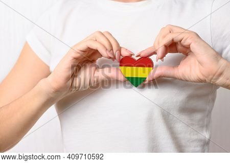 Love Bolivia. The girl holds a heart in the form of the flag of Bolivia on her chest. Bolivian patriotism concept