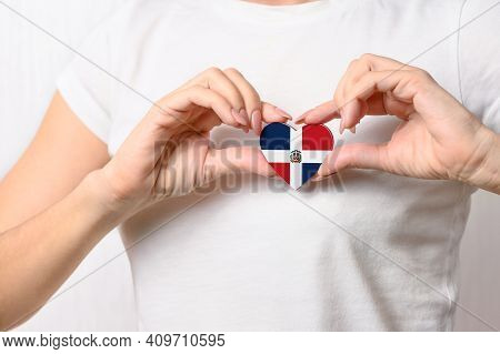 Love the Dominican Republic. The girl holds a heart in the form of the flag of Dominican Republic on her chest. Dominican patriotism concept