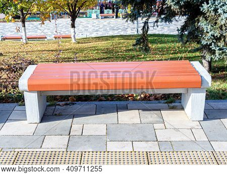Wooden Bench At The City Street In Summer Sunny Day