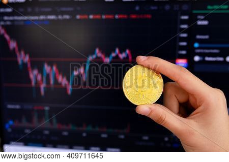 Hand Holding Bitcoin In Front Of The Graph With The Exchange Rate. Bitcoin Cryptocurrency Gold Coin.