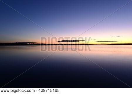 Blue Sky In The Orange Twilight Glow On Horizon Over Calm Azure Water Lake
