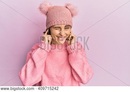 Young brunette woman wearing cute wool cap covering ears with fingers with annoyed expression for the noise of loud music. deaf concept.