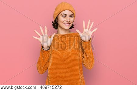 Young hispanic woman wearing casual clothes and wool cap showing and pointing up with fingers number ten while smiling confident and happy.