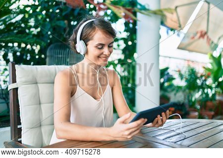 Young beautiful caucasian woman smiling happy at home using touchpad and listening to music wearing headphones