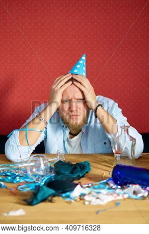 Man Suffering From Hangover At Table With Blue Cap In Messy Room After Birthday Party