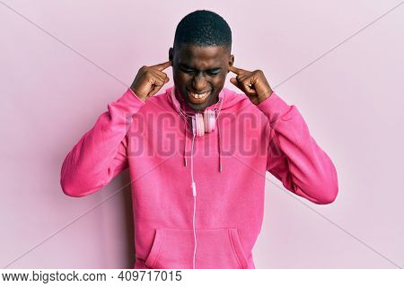 Young african american man wearing gym clothes and using headphones covering ears with fingers with annoyed expression for the noise of loud music. deaf concept.