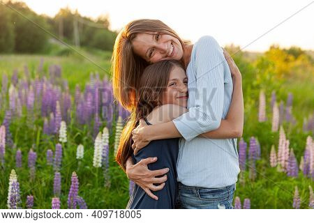 Young Mother Embracing Her Child Outdoor. Woman And Teenage Girl On Summer Field With Blooming Wild