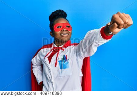 African american doctor woman wearing medical coat and super hero mask and coat doing power gesture