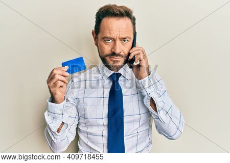 Middle age businessman talking on the smartphone holding credit card relaxed with serious expression on face. simple and natural looking at the camera.