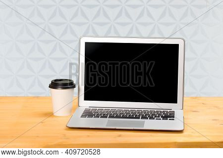Mockup Blank Laptop Screen With Coffee On Wooden Table In Coworking Space.