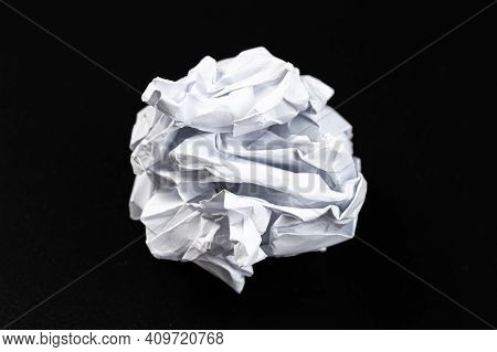 A Crumpled Paper Ball In A Black Background