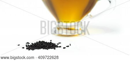 A Handful Of Black Cumin Seeds On The Background Of A Glass Gravy Boat With Black Seed Oil. Selectiv