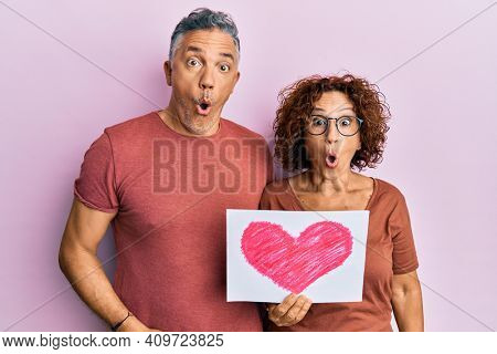 Beautiful middle age couple holding heart draw scared and amazed with open mouth for surprise, disbelief face