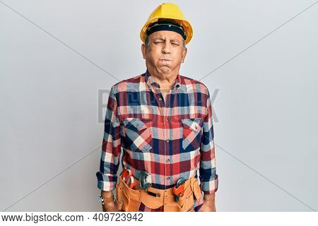 Senior hispanic man wearing handyman uniform puffing cheeks with funny face. mouth inflated with air, crazy expression.