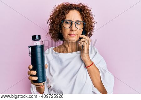 Beautiful middle age mature woman using smartphone holding water bottle relaxed with serious expression on face. simple and natural looking at the camera.