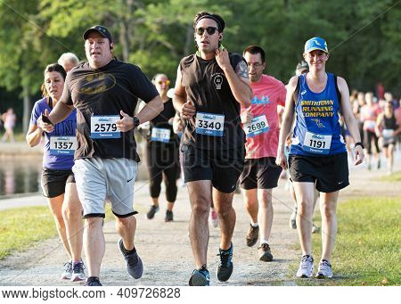 North Babylon, New York, Usa - 8 July 2019: Front View Of A Group Of Runners Running A 5k Trail Race